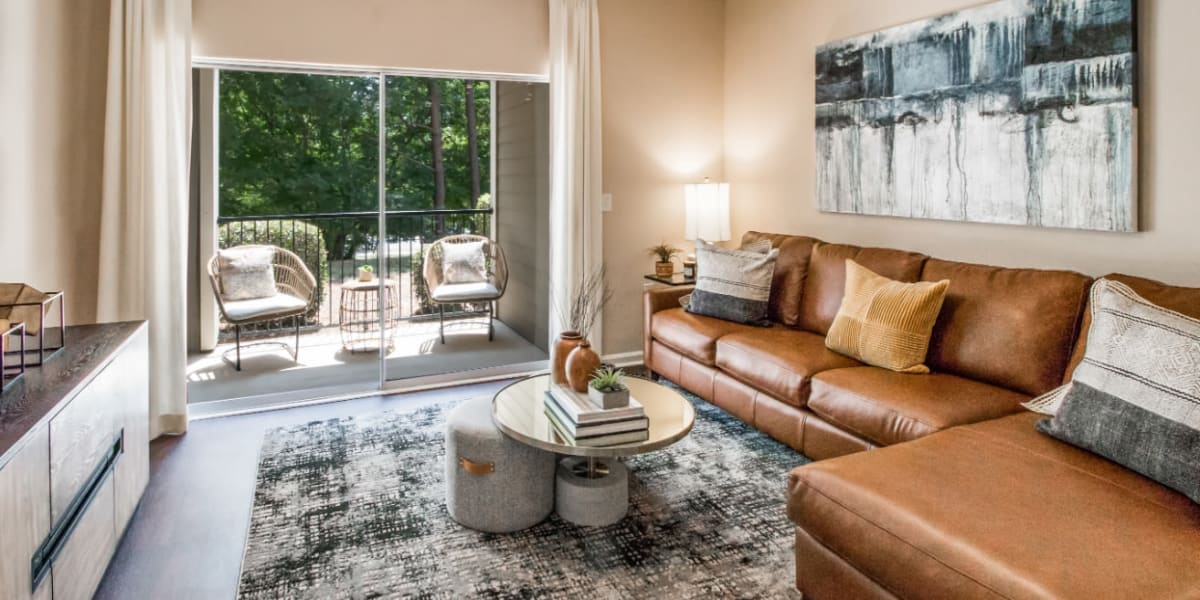Sleek and modern style living room with private patio at Marquis at Carmel Commons in Charlotte, North Carolina