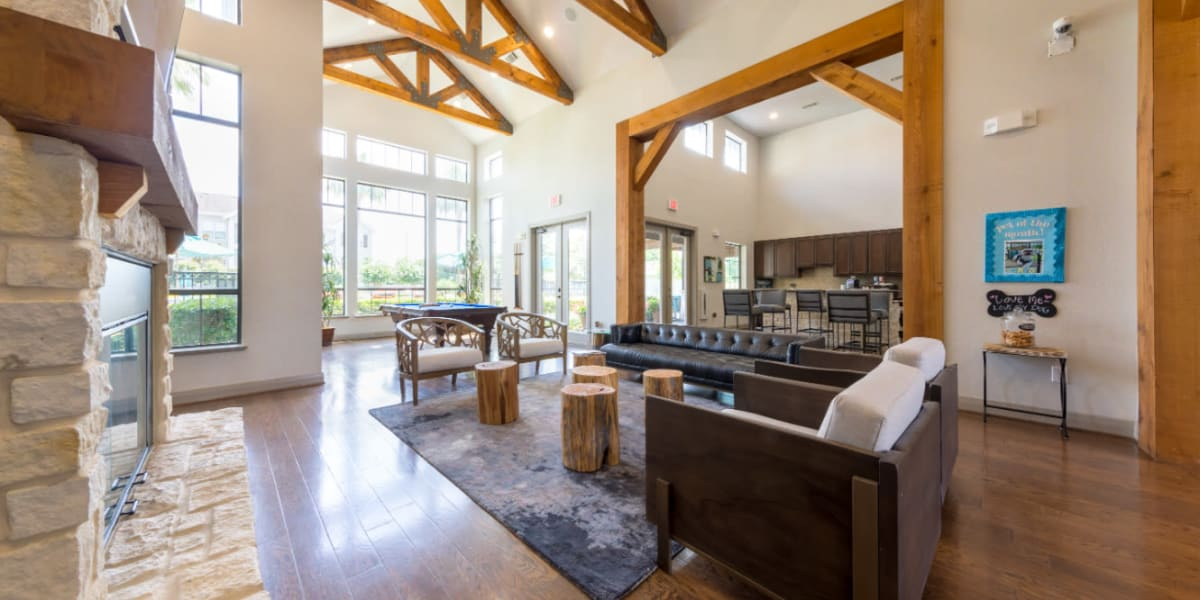 Community clubhouse sitting area with stone fireplace overlooking dining area at Marquis at Sugar Land in Sugar Land, Texas