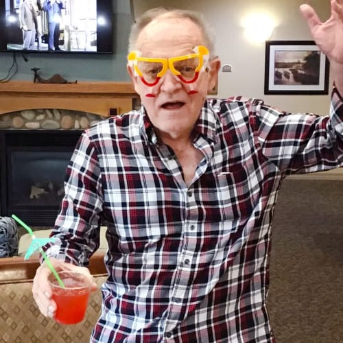 Resident partying with a drink in hand at Glen Carr House Memory Care in Derby, Kansas