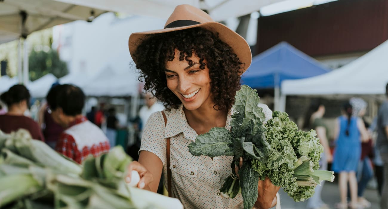Woman out at the local outdoor market picking up some kale in Little Falls, New Jersey near Park Lane Apartments