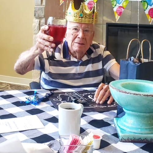 Resident wearing a crown and raising a goblet at The Oxford Grand Assisted Living & Memory Care in McKinney, Texas