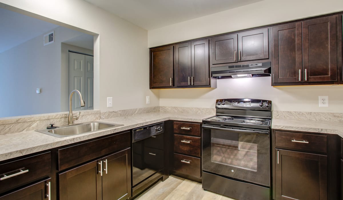 Kitchen with dark cabinets and nice oven at Kensington at Beverly Hills in Southfield, Michigan