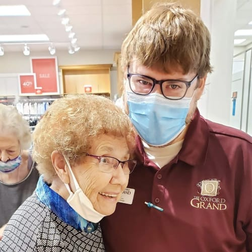 Happy resident hugging a masked caretaker at The Oxford Grand Assisted Living & Memory Care in Wichita, Kansas