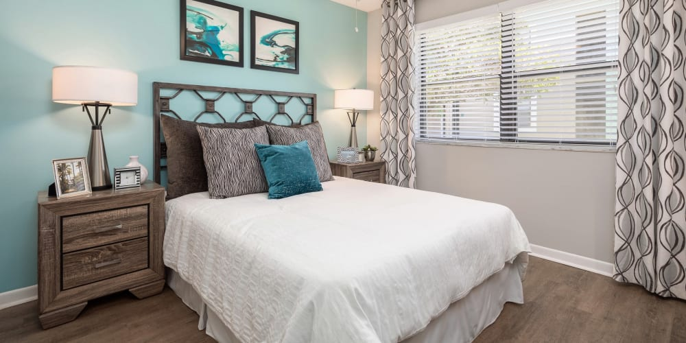 Well-furnished primary bedroom with an accent wall in a model apartment at The EnV in Hollywood, Florida