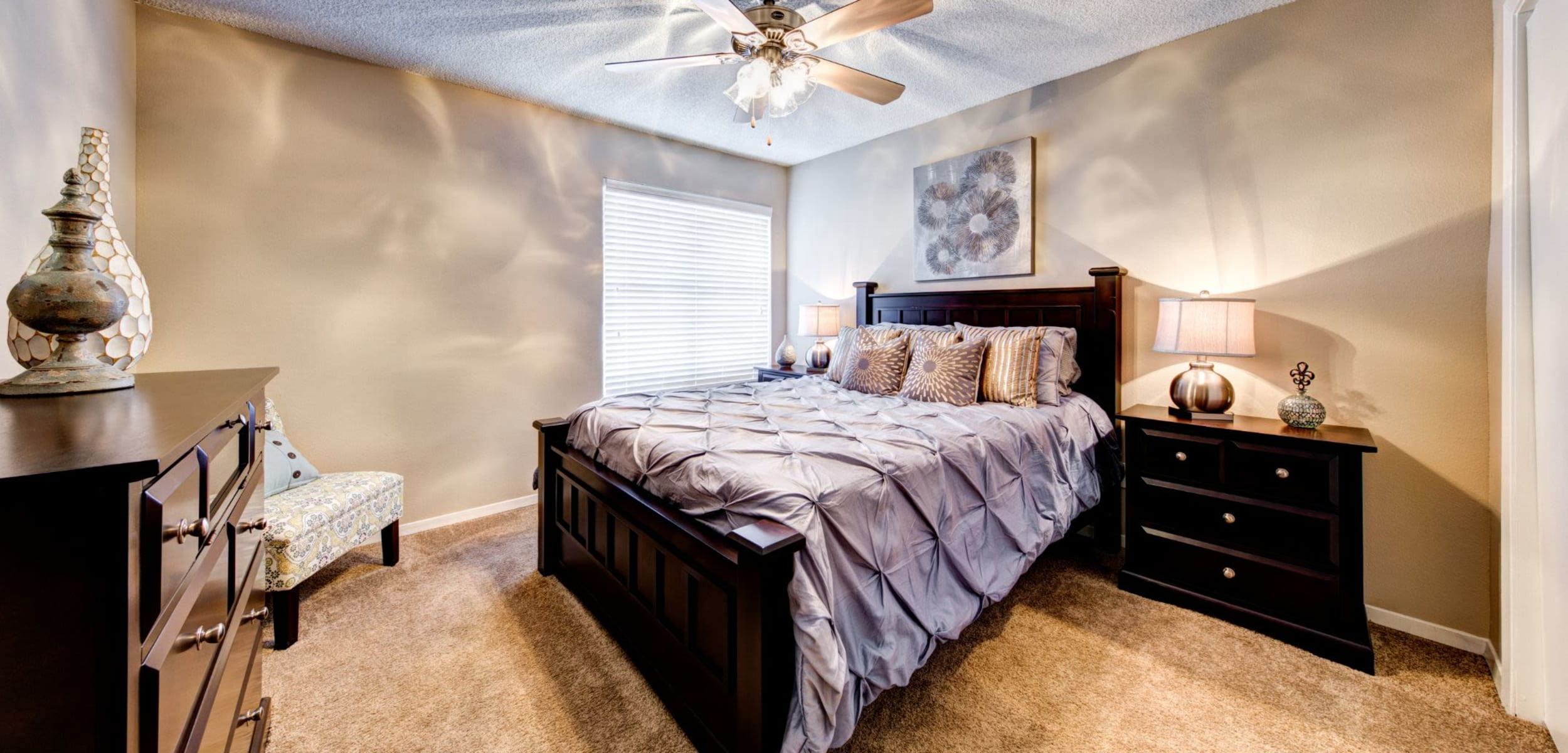 Bright bedroom with a ceiling fan at The Park at Flower Mound in Flower Mound, Texas