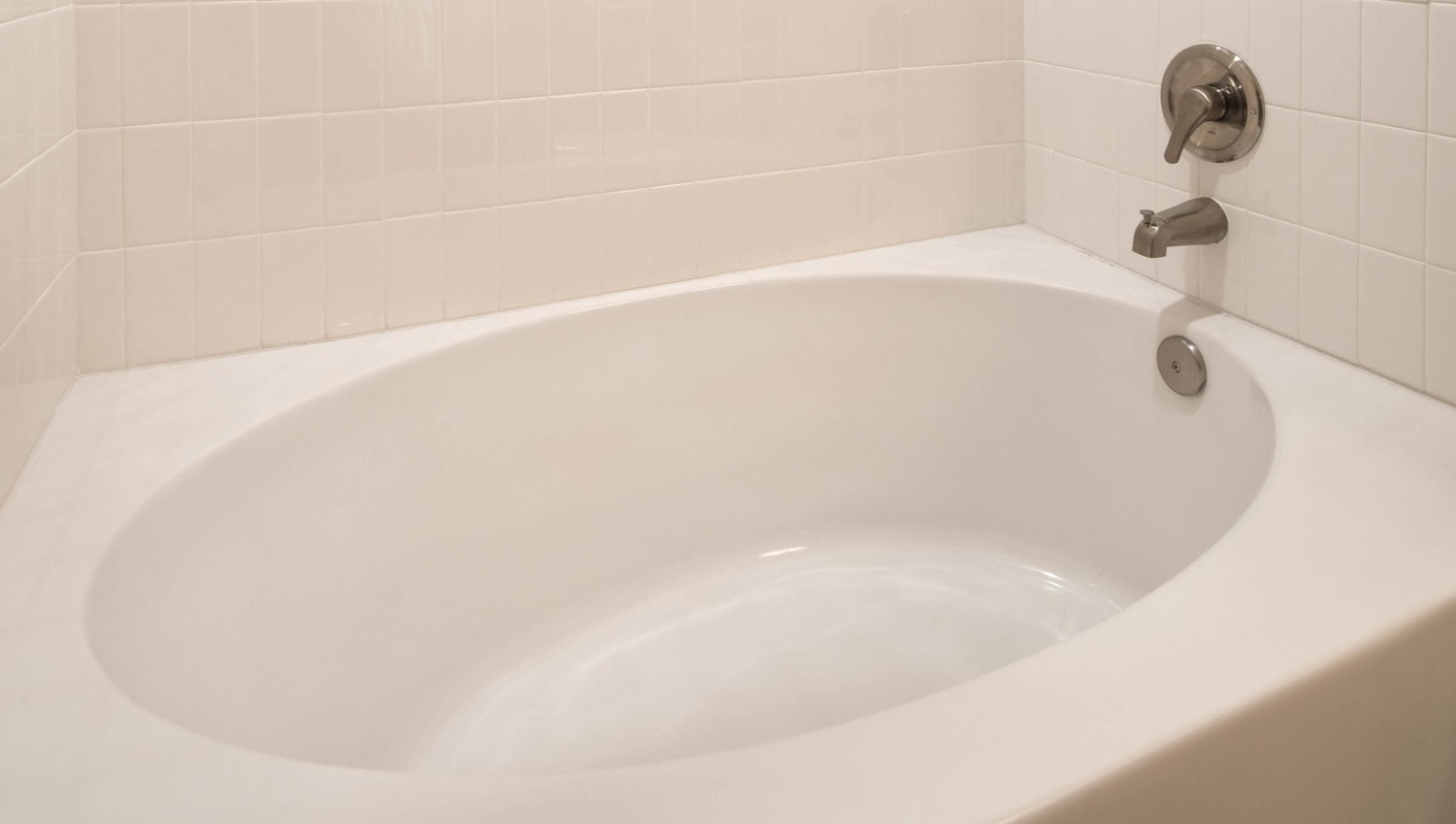 Oval soaking tub in the master bathroom of a model apartment at Olympus Waterford in Keller, Texas