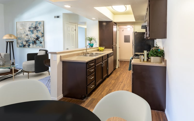 Kitchen with a view into the living room at Shadowbrook Apartments in West Valley City, Utah