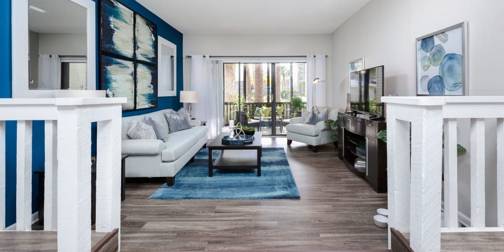 Large living room with wood floors and patio access at Enclave at Lake Ellenor in Orlando, Florida