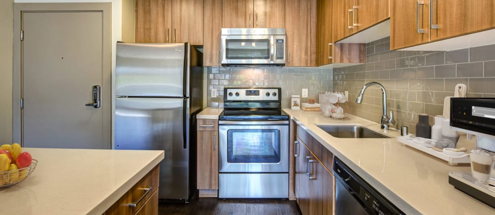 A kitchen with quartz countertops and stainless steel appliances at Harborside Marina Bay Apartments in Marina del Rey, California