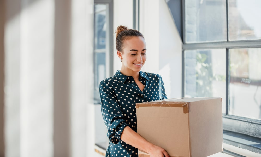 A women moving boxes from her office to a Cedartree Management Company location