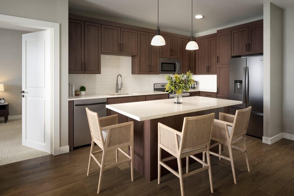 Kitchen with a stone-surface island and dark hardwood flooring at Amira Minnetonka in Minnetonka, Minnesota