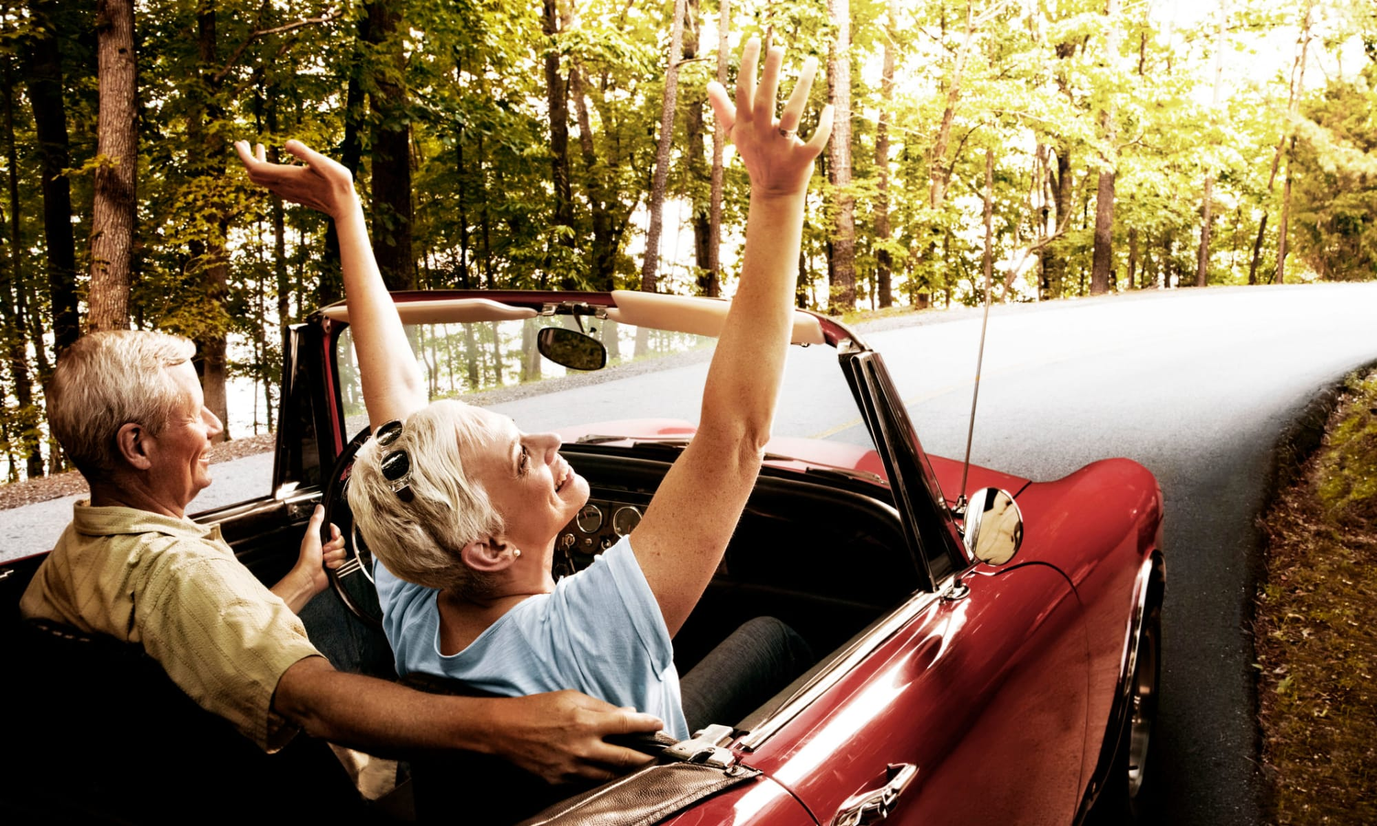 background image of seniors driving in a convertible car