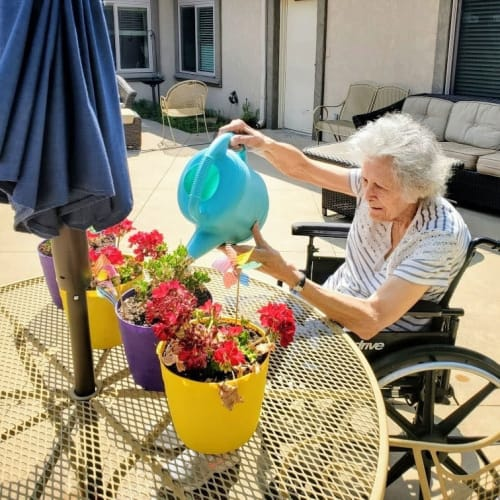 A Resident watering some flowers outside at Glen Carr House Memory Care in Derby, Kansas