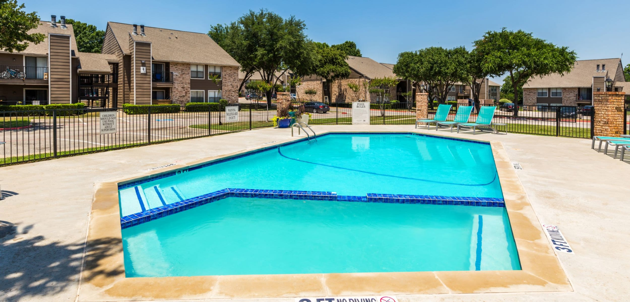Bright pool with sun chairs at The Park at Flower Mound in Flower Mound, Texas
