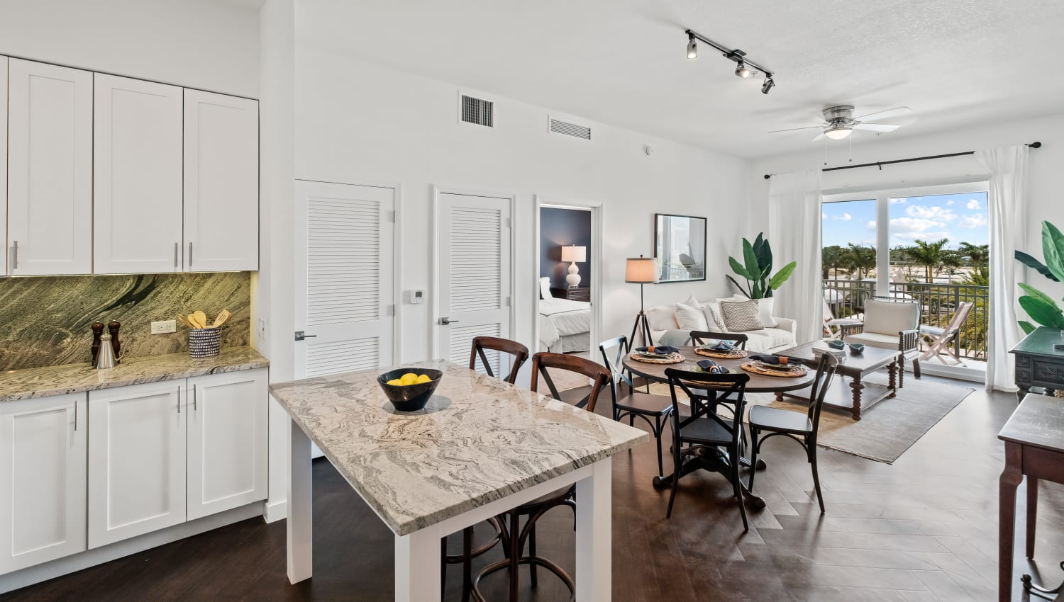 Open dining and living area with private balcony access at Town Lantana in Lantana, Florida