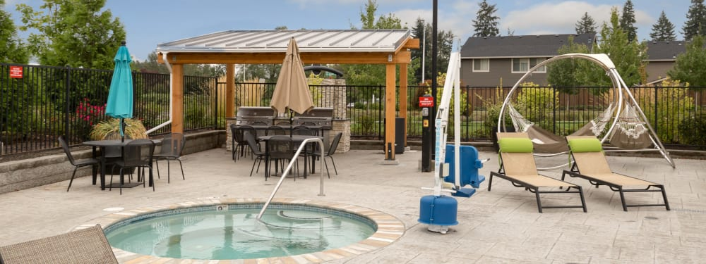Hot tub, BBQ pit, tables, and cozy landscaping at Terrene at the Grove in Wilsonville, Oregon