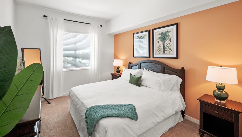 Well lit model bedroom with plush carpeting at Town Lantana in Lantana, Florida