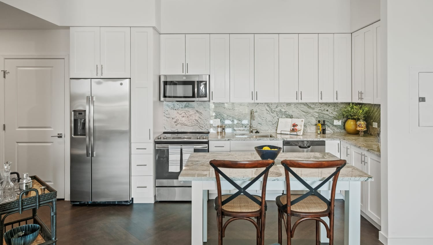 Model kitchen with white cabinetry and quartz countertops and full-height backsplashes at Town Lantana in Lantana, Florida
