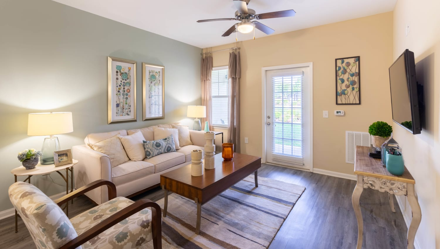 Model home's living space with an accent wall and hardwood floors at Legends at White Oak in Ooltewah, Tennessee