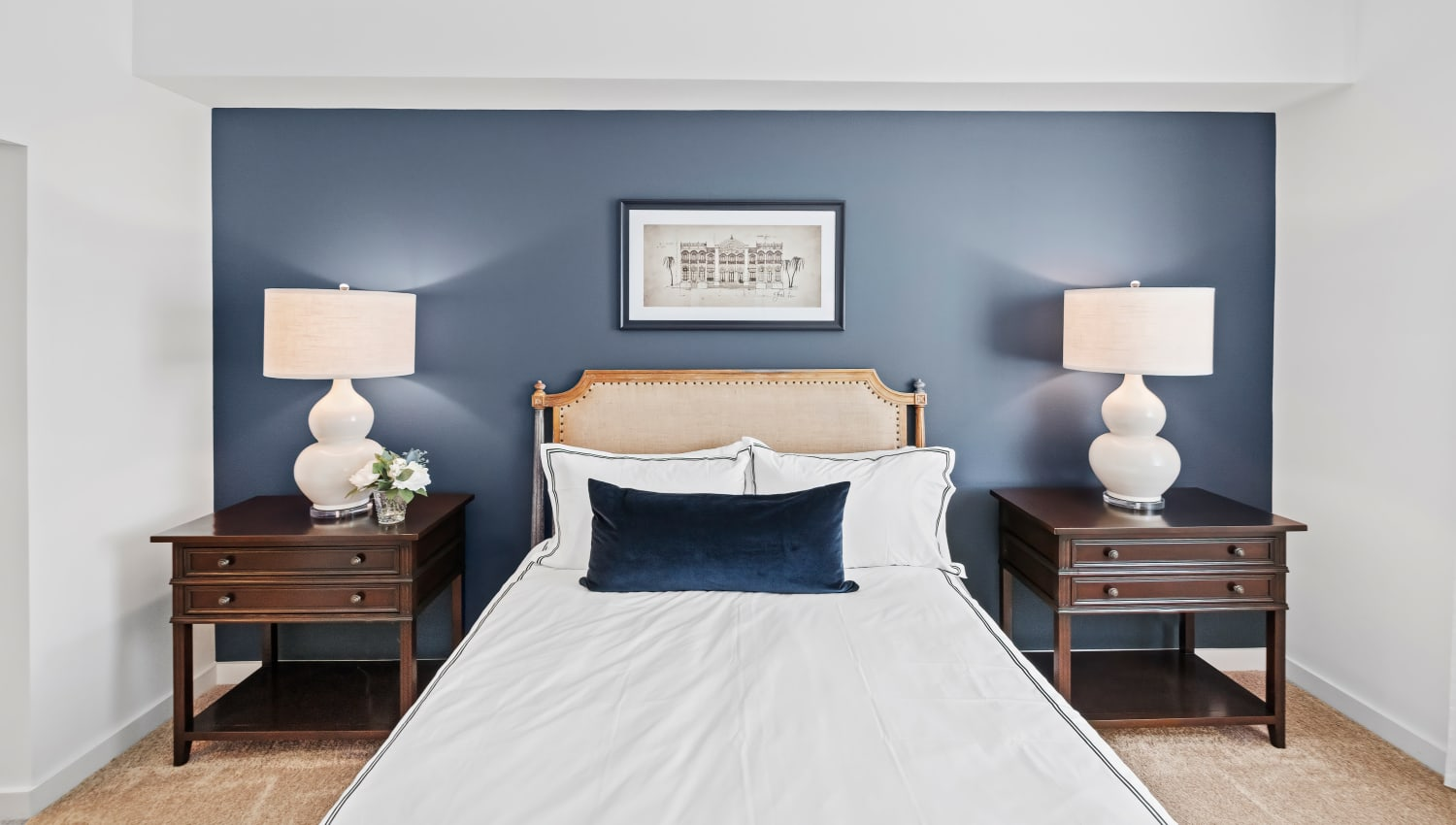 Model bedroom with a deep blue accent wall and two bedside tables at Town Lantana in Lantana, Florida