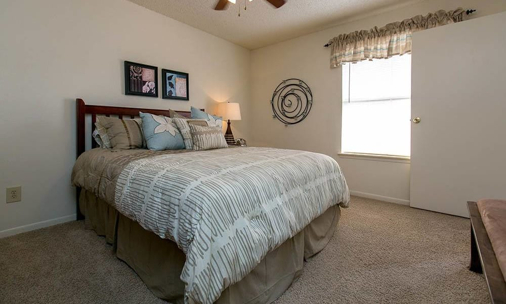 Bedroom with a ceiling fan at Walnut Ridge Apartments in Corpus Christi, Texas