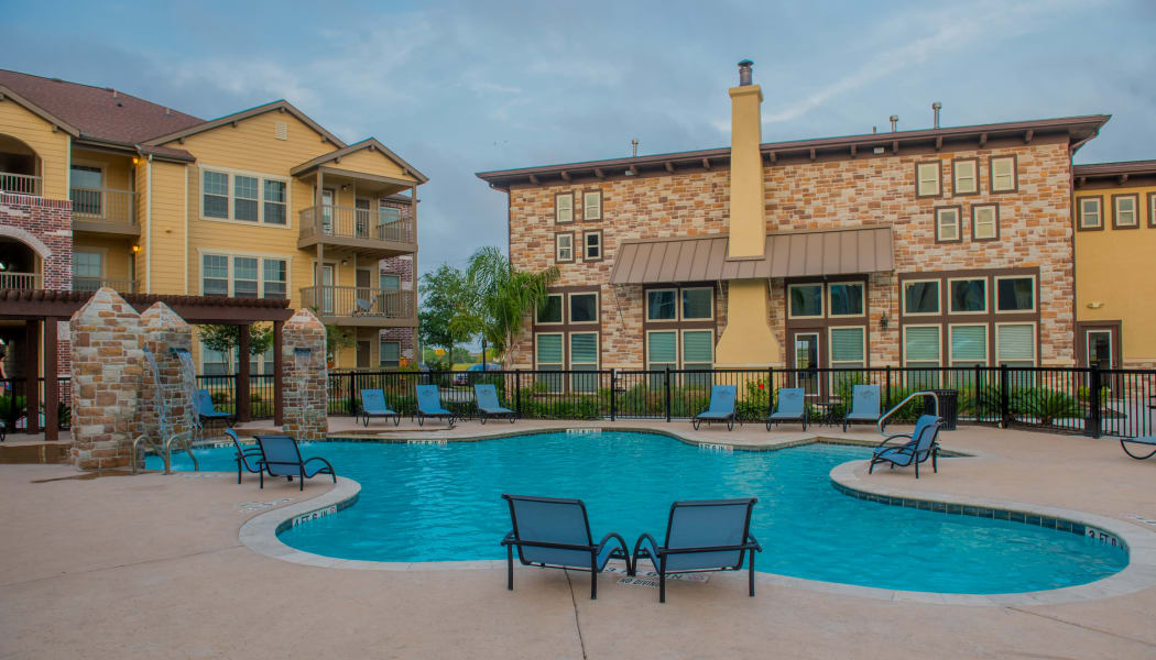 Sparkling swimming pool with poolside seating at Tuscana Bay Apartments in Corpus Christi, Texas