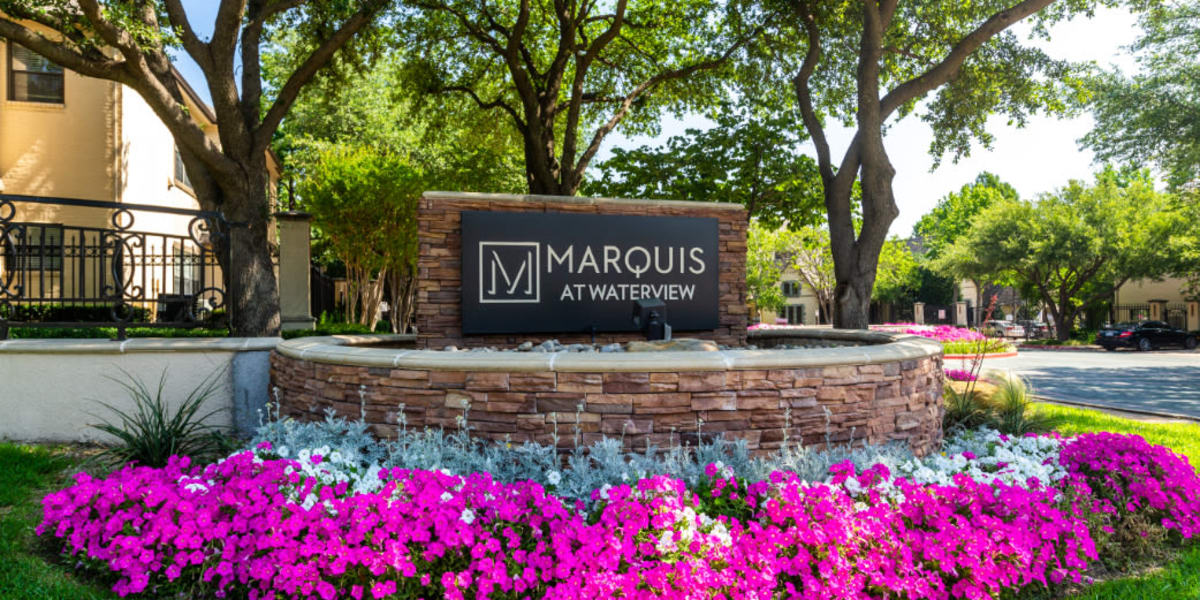 Property stone sign surrounded by colorful flowers and plants at Marquis at Waterview in Richardson, Texas