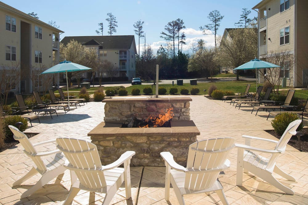 Outdoor fireplace with plenty of seating at Park Villas Apartments in Lexington Park, Maryland