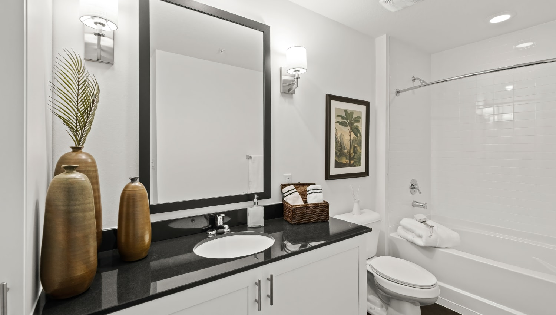 Elegant bathroom with oversized vanity and tiled tub surround at Town Lantana in Lantana, Florida