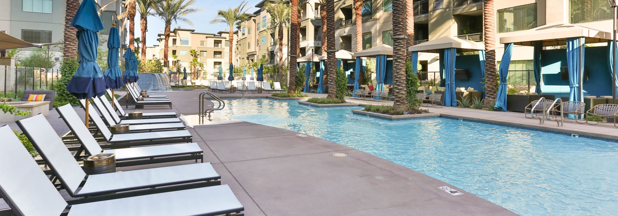 Chaise lounge chairs lined up by the swimming pool at Avant at Fashion Center in Chandler, Arizona