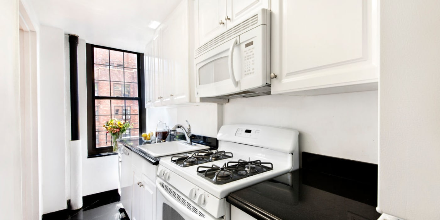 Kitchen with white cabinets and white appliances at London Terrace Gardens in New York, New York