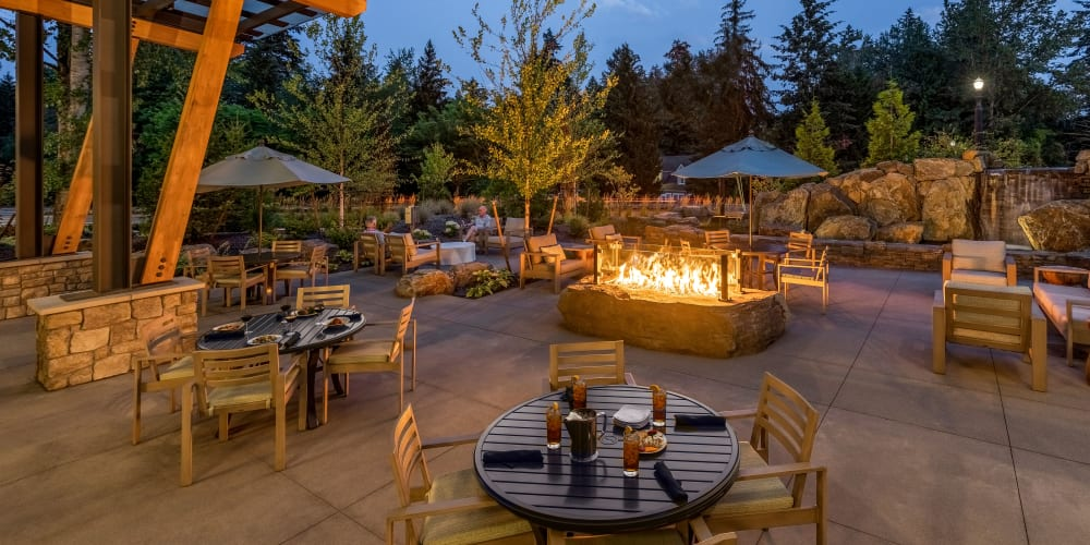 warmly lit patio with covered seating and a fire pit at The Springs at Lake Oswego in Lake Oswego, Oregon