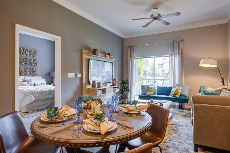 Well-furnished model home's dining and living area at Celsius Apartment Homes in Charlotte, North Carolina