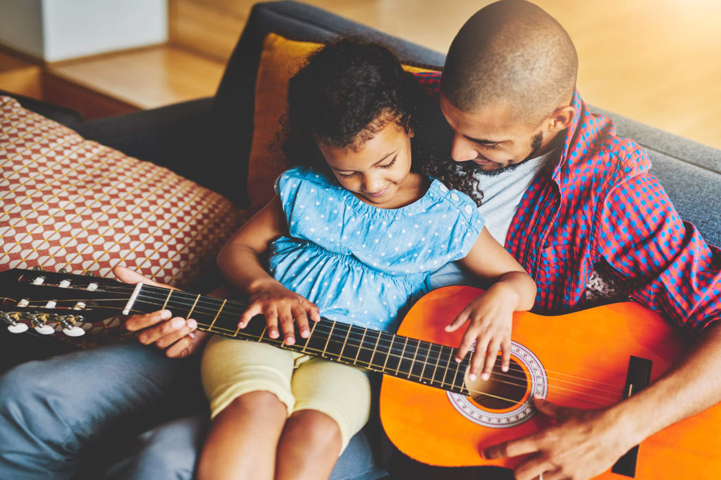 Father teaching his daughter to play guitar at Castlewood Apartments in Walnut Creek, California