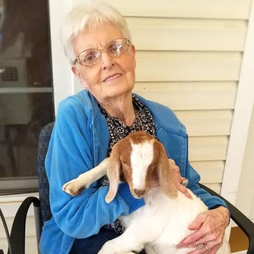 Resident sitting outside holding a small goat at Creekside Village in Ponca City, Oklahoma