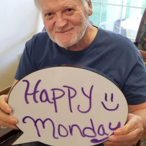 A resident holding a sign that says ' happy monday' at Creekside Village in Ponca City, Oklahoma