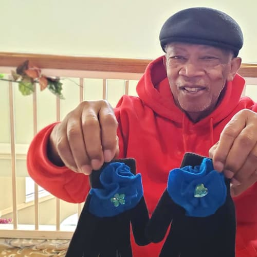 Resident holding up a pair of winter gloves at Canoe Brook Assisted Living & Memory Care in Catoosa, Oklahoma