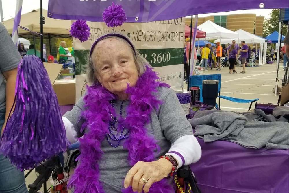 A resident dressed with purple accessories for an event at The Meadowlands in O'Fallon, Missouri