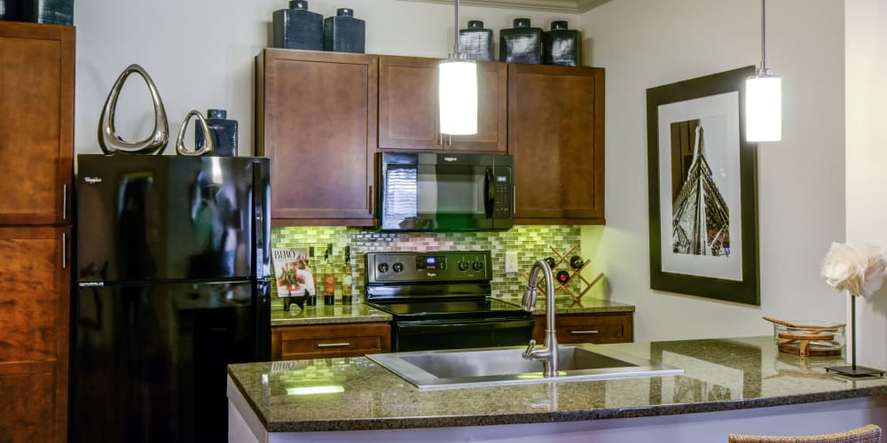 Granite countertop kitchen with bar seating at Firewheel Apartments in San Antonio