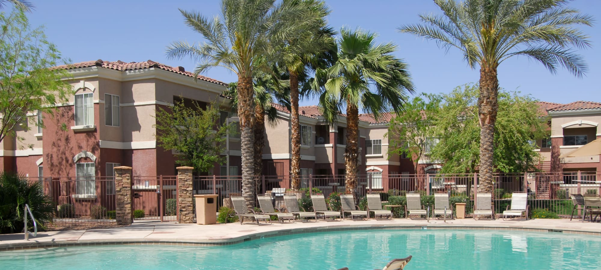 Lounge chairs lining the resort-style swimming pool at Remington Ranch in Litchfield Park, Arizona