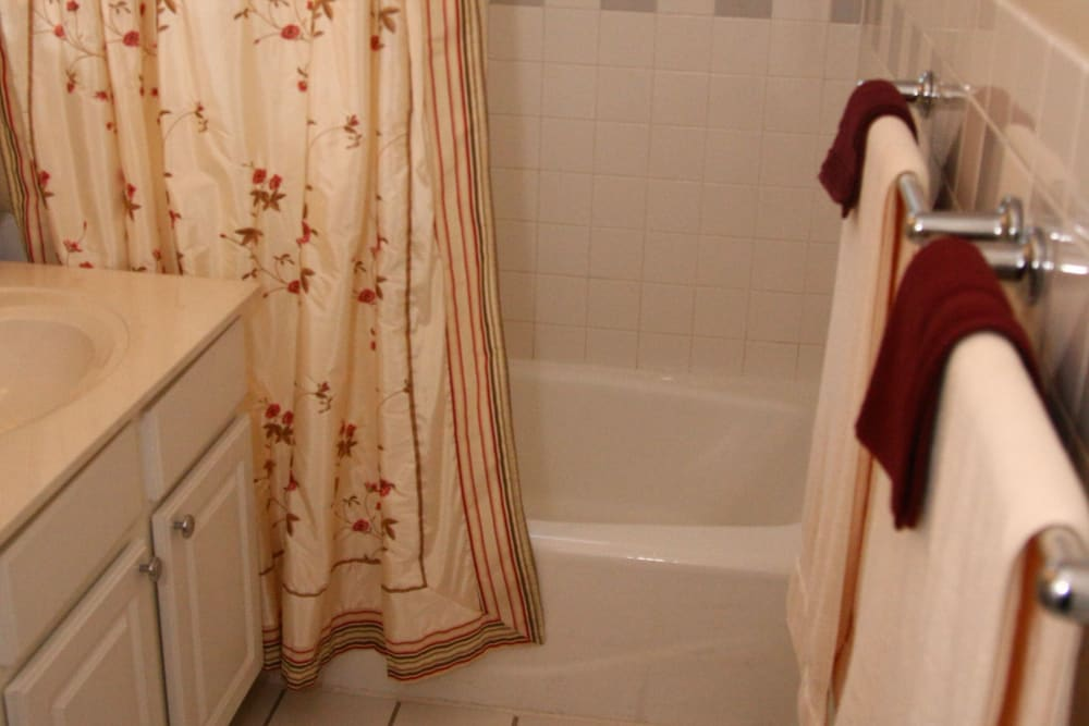 White tub and floral shower curtain at Jackson House Apartments