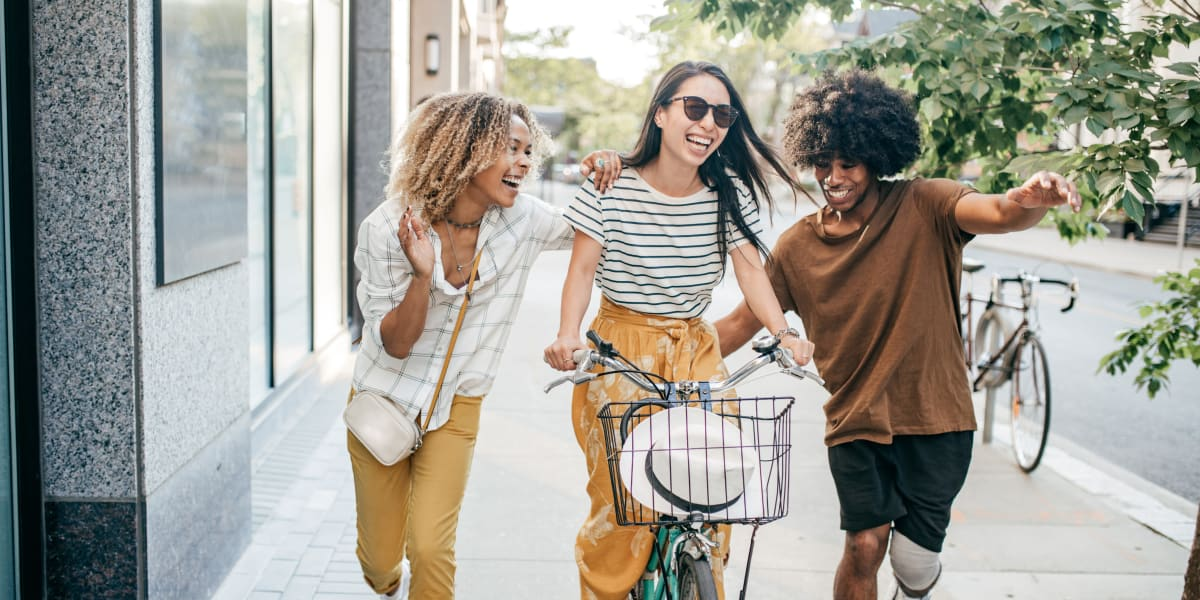 Young woman riding bike with two friends on each side near Marquis at Carmel Commons in Charlotte, North Carolina