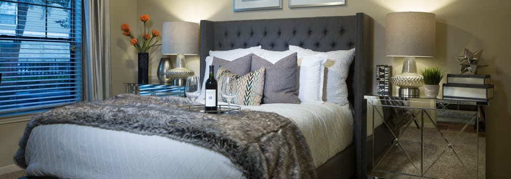 A spacious bedroom with plush carpeting at Sommerall Station Apartments in Houston, Texas