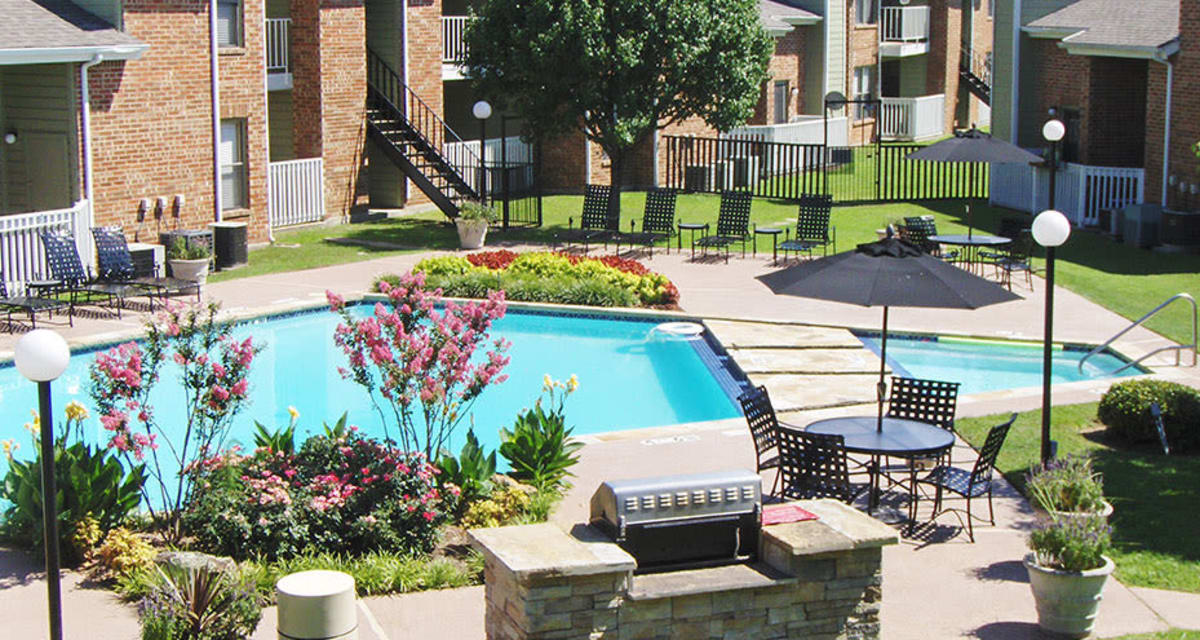 BBQ area by the pool at Greentree Apartments  in  Carrollton, Texas