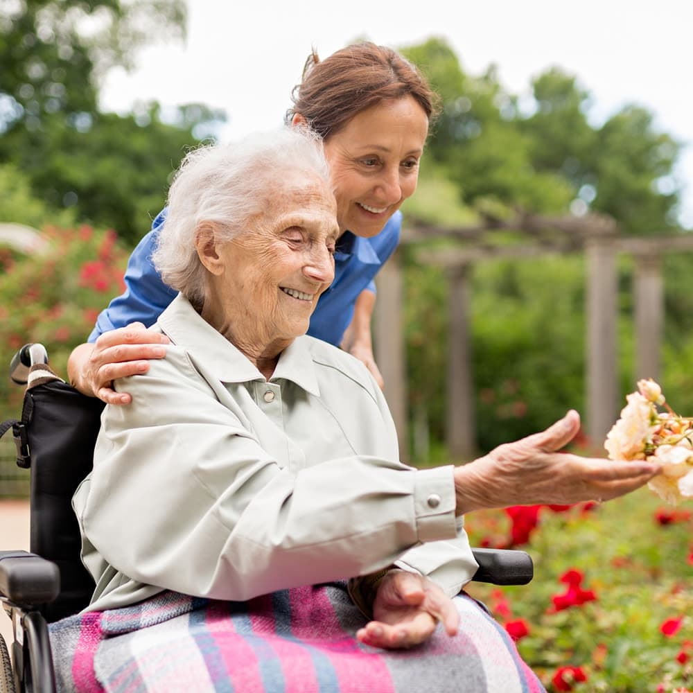 Senior picking flowers with nurse at The Commons at Dallas Ranch in Antioch, California