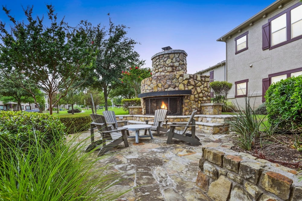 Stone wall outdoor fire pit with seating at Ranch ThreeOFive in Arlington, Texas