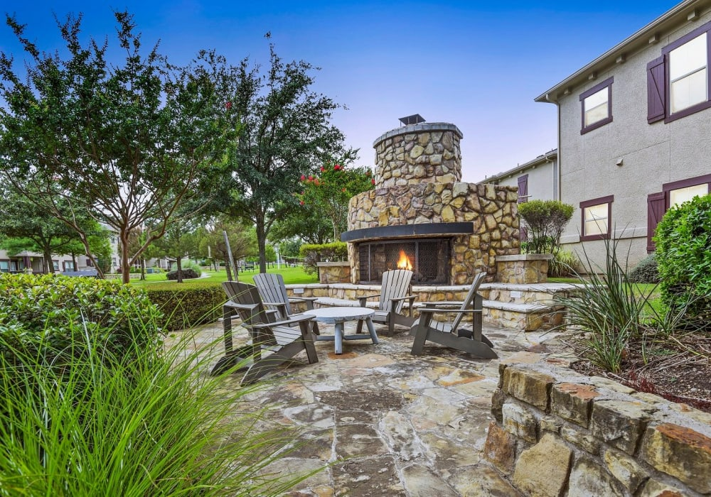 Outdoor stone-wall fire pit with seating at Ranch ThreeOFive in Arlington, Texas
