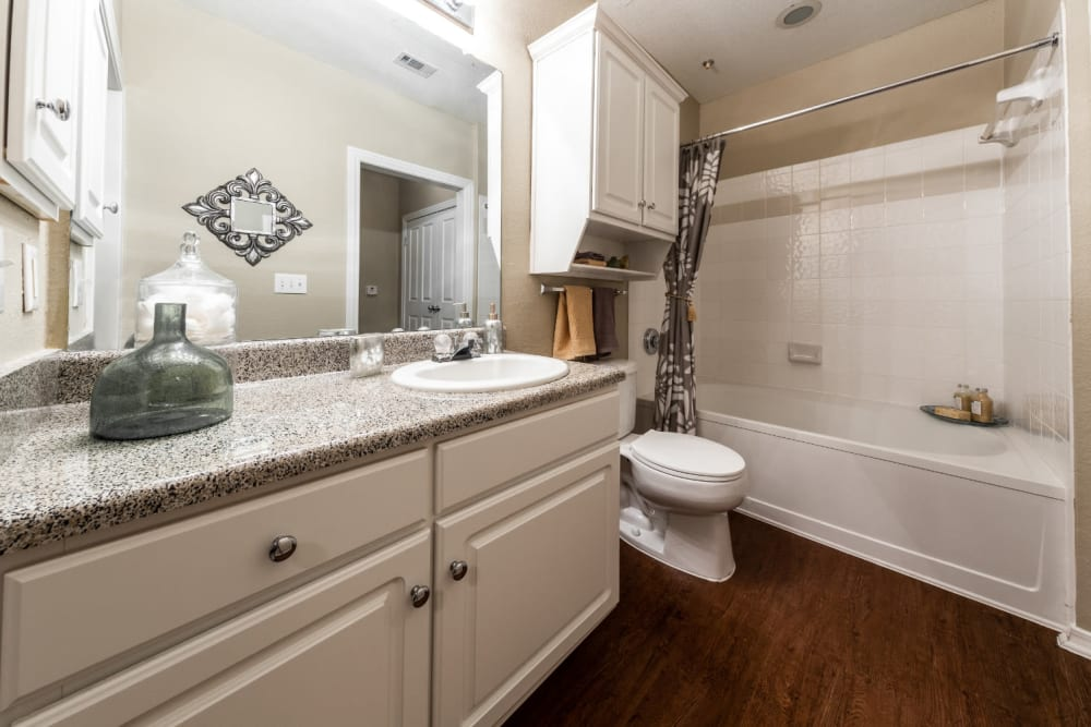 Bright bathroom with wood flooring and bathtub at Marquis at Waterview in Richardson, Texas