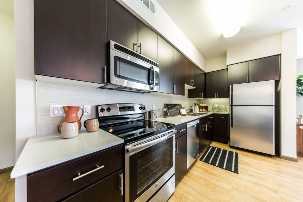 Modern style kitchen with stainless steel appliances and wood flooring at Marquis at Desert Ridge in Phoenix, Arizona
