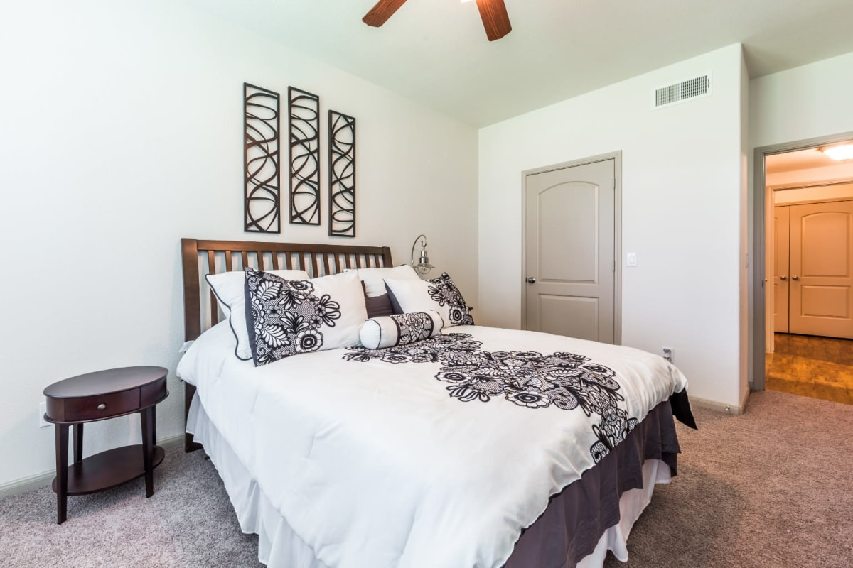 Carpeted bedroom with walk-in closet at Marquis at Clear Lake in Webster, Texas